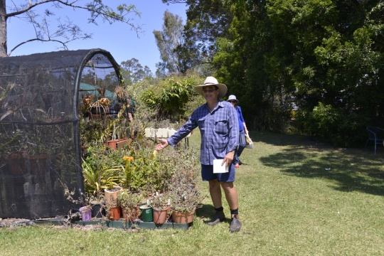 Paul Forster showing us his plants growing in green houses spread over his property.
